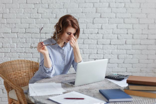young woman aspiring author having a difficult time in front of her laptop