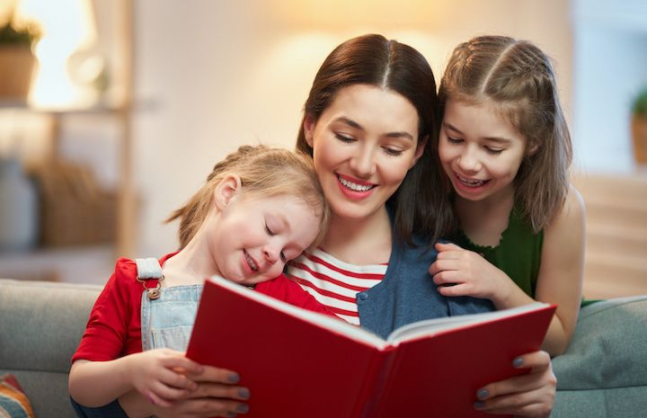 mother reading a book to her two daughters